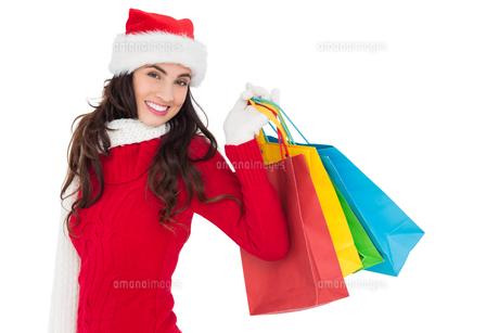 Festive brunette in winter wear holding shopping bagsの写真素材 [FYI00004525]