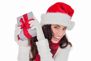Happy brunette in santa hat holding giftの写真素材 [FYI00004526]