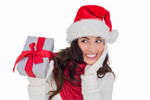Surprised brunette in santa hat holding giftの写真素材 [FYI00004527]