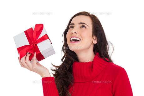 Happy brunette in red jumper hat showing a giftの写真素材 [FYI00004528]