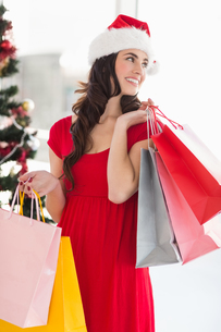 Brunette in red dress holding shopping bagsの写真素材 [FYI00004529]
