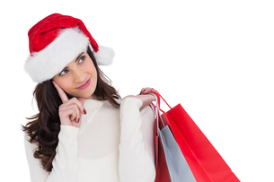 Festive brunette holding shopping bags and thinkingの写真素材 [FYI00004532]