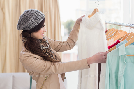 Pretty shopping brunette looking at dressの写真素材 [FYI00004534]