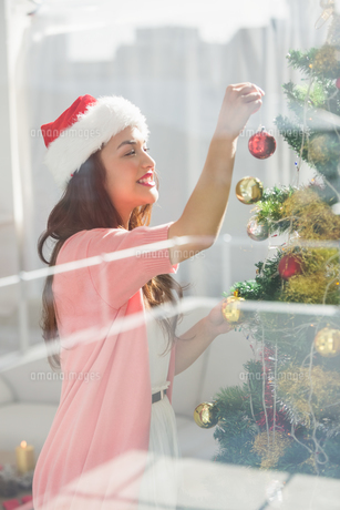 Festive brunette decorating a christmas treeの素材 [FYI00004540]