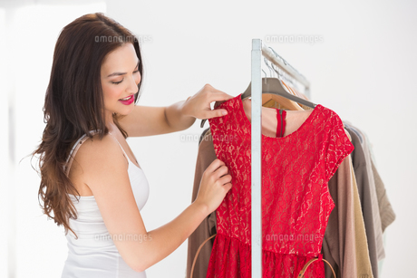 Pretty shopping brunette looking at red dressの写真素材 [FYI00004543]