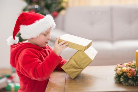 Festive little boy opening a giftの写真素材 [FYI00004547]