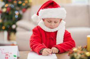 Festive little boy writing wish listの写真素材 [FYI00004552]