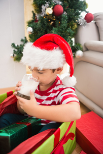 Cute boy in large christmas present drinking milkの素材 [FYI00004560]