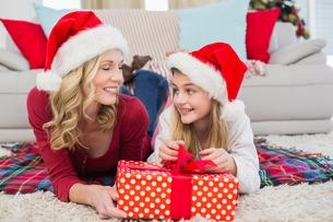 Festive little girl opening a gift with motherの写真素材 [FYI00004570]
