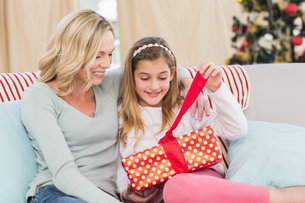 Cute little girl sitting on couch opening gift with mumの写真素材 [FYI00004572]