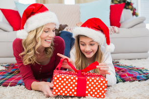 Festive little girl opening a gift with motherの写真素材 [FYI00004573]