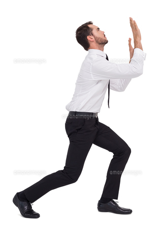 Businessman standing with bent legs and pushingの写真素材 [FYI00004586]