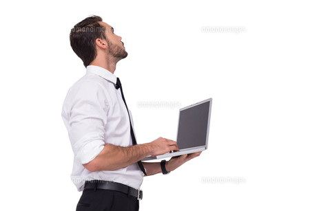 Sophisticated businessman standing using a laptopの写真素材 [FYI00004589]