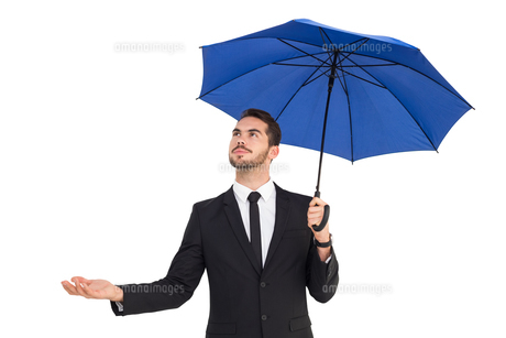 Cheerful businessman holding umbrella with hand outの写真素材 [FYI00004595]
