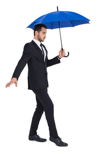 Concentrated businessman holding umbrella while steppingの写真素材 [FYI00004596]