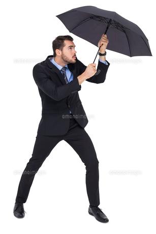 Businessman holding umbrella to protect himselfの写真素材 [FYI00004597]