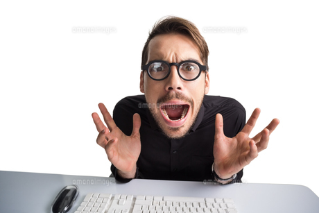 Worried businessman with glasses using computerの写真素材 [FYI00004599]