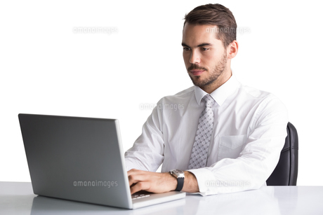 Cheerful businessman using laptop at deskの写真素材 [FYI00004602]
