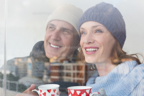Happy couple in warm clothing holding mugsの写真素材 [FYI00004607]