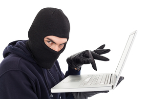 Hacker in balaclava standing and typing on laptopの写真素材 [FYI00004608]