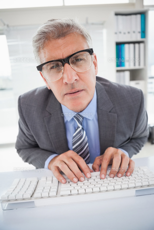 Focused businessman typing at his deskの写真素材 [FYI00004610]