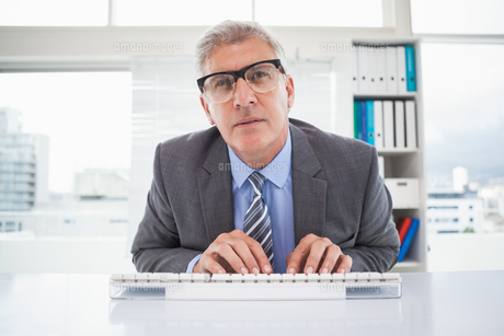 Focused businessman typing at his deskの写真素材 [FYI00004611]