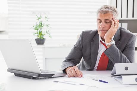 Tired businessman falling asleep at deskの写真素材 [FYI00004621]