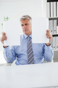Mature businessman looking at two pagesの写真素材 [FYI00004623]