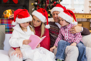 Festive family wearing santa hat while reading on the couchの写真素材 [FYI00004641]