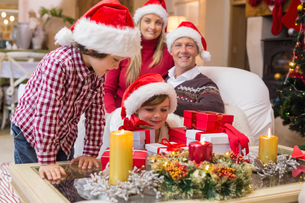 Smiling family at christmas time with lots of presentsの写真素材 [FYI00004642]