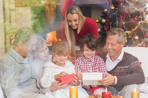 Multi generation family opening presents on sofaの写真素材 [FYI00004649]