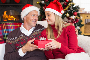 Smiling couple in santa hat holding presentの写真素材 [FYI00004654]