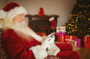 Concentrated santa using smartphone at christmasの写真素材 [FYI00004670]