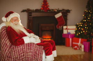 Festive santa claus sitting on couch at christmasの写真素材 [FYI00004671]