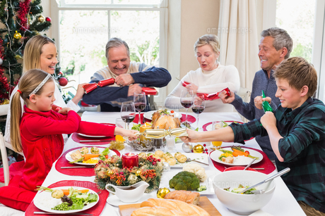 Family pulling christmas crackers at the dinner tableの写真素材 [FYI00004672]