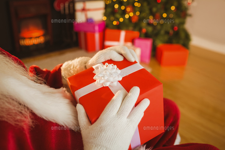 Santa claus holding a red giftの写真素材 [FYI00004674]