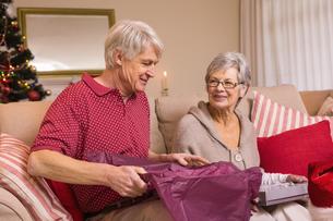 Senior couple opening a christmas present on sofaの写真素材 [FYI00004686]
