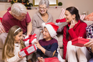 Multi generation family exchanging presents on sofaの写真素材 [FYI00004687]