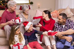 Multi generation family exchanging presents on sofaの写真素材 [FYI00004688]