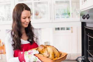 Happy woman holding roast turkeyの写真素材 [FYI00004690]