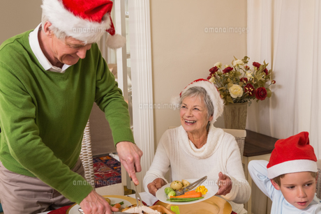 Grandfather in santa hat serving roast turkey at christmasの写真素材 [FYI00004698]
