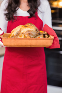 Mid section of woman holding roast turkeyの写真素材 [FYI00004699]