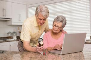 Senior couple looking up medication onlineの写真素材 [FYI00004703]