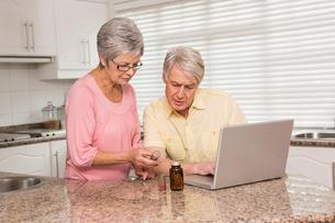 Senior couple looking up medication onlineの写真素材 [FYI00004707]