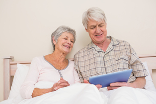 Senior couple relaxing in bed using tablet pcの写真素材 [FYI00004713]