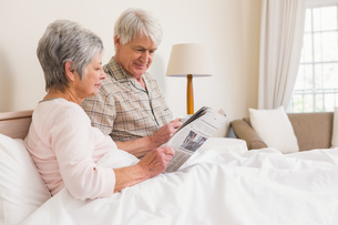 Senior couple relaxing in bedの写真素材 [FYI00004717]