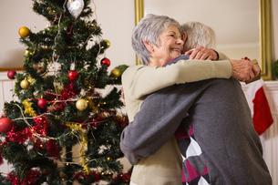 Senior couple hugging beside their christmas treeの素材 [FYI00004721]