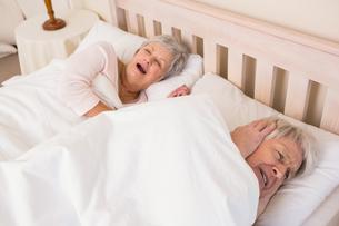 Senior man blocking out his wifes snoringの写真素材 [FYI00004724]
