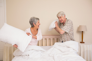Senior couple having a pillow fightの写真素材 [FYI00004726]