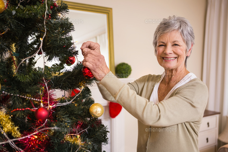 Senior woman decorating the christmas treeの素材 [FYI00004728]